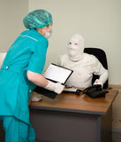 Patient similar to a mummy and the doctor. The patient similar to a mummy and the doctor, at office stock photo