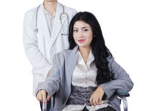Patient sits on wheelchair with doctor in studio Stock Photo
