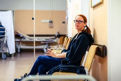 Patient sitting in hospital ward hallway waiting room with iv. royalty free stock photography