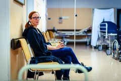 Patient sitting in hospital ward hallway waiting room with iv. royalty free stock photo