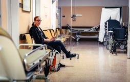 Patient sitting in hospital ward hallway waiting room with iv. stock image