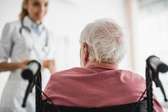 Patient sitting in wheelchair and looking at doctor royalty free stock photo