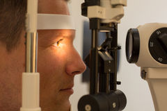 Patient at slit lamp of optician or optometrist Stock Image