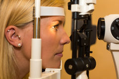 Patient at slit lamp of optician or optometrist stock images