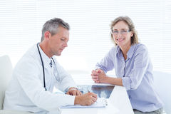 Patient smiling at camera while doctor taking notes Stock Images