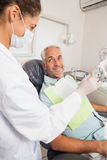 Patient smiling at dentist in the chair Stock Image