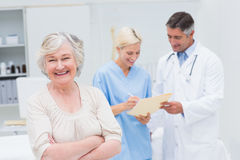 Patient smiling while doctor and nurse discussing in clinic. Portrait of senior female patient smiling while doctor and nurse discussing in background at clinic Stock Photography