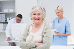 Patient smiling while doctor and nurse working in background. Portrait of senior patient smiling while doctor and nurse working in background at clinic Stock Images