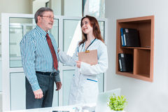Patient smiling to his doctor in medical office Royalty Free Stock Photos