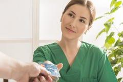 Patient som betalar för en medicinsk konsultation med kreditkorten Royaltyfria Bilder