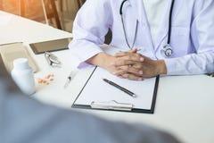 patient som fast beslutsamt lyssnar till en förklarande patient s för manlig doktor Arkivfoto