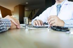 patient som fast beslutsamt lyssnar till en förklarande patient s för manlig doktor Arkivbild