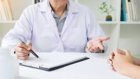 patient som fast beslutsamt lyssnar till en förklarande patient s för manlig doktor Arkivbilder