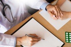 patient som fast beslutsamt lyssnar till en förklarande patient s för manlig doktor Royaltyfri Foto