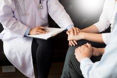 patient som fast beslutsamt lyssnar till en förklarande patient s för manlig doktor Arkivfoton