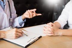 patient som fast beslutsamt lyssnar till en förklarande patient s för manlig doktor Royaltyfri Bild
