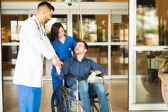 Patient som lämnar sjukhuset på en rullstol Royaltyfri Bild