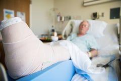 Patient som ligger i sjukhussäng med benbrottbenet som slås in i ca arkivbilder