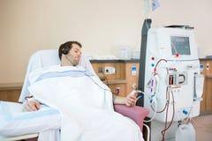 Patient som lyssnar till musik, medan motta som är njur- Royaltyfri Foto