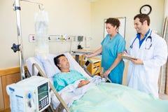 Patient som ser medicinska Team In Hospital Room royaltyfri bild