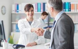 Patient som skakar händer med en kvinnlig doktor Arkivbild