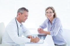 Patient souriant à l'appareil-photo tandis que docteur prenant des notes images stock
