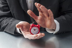 Patient or stressed out businessman with symbol of time in hands Royalty Free Stock Photos