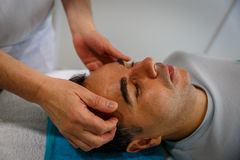 A patient on a stretcher attended by his therapist Stock Images