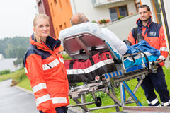 Patient on stretcher with paramedics emergency aid. Patient on stretcher with paramedics ambulance aid emergency women man royalty free stock photos