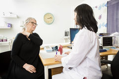 Patient Suffering From Shoulder Pain While Looking At Doctor. Senior female patient suffering from shoulder pain while looking at doctor in clinic royalty free stock photos