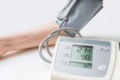 Patient suffers from hypertension. Woman is measuring blood pressure with monitor Stock Image