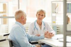 Patient supérieur à la visite médicale photographie stock