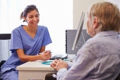 Patient supérieur ayant la consultation avec l'infirmière In Office Photo stock