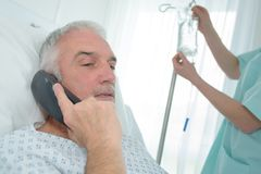 Patient supérieur dans l'hôpital utilisant le téléphone photo libre de droits