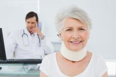 Patient supérieur dans le collier chirurgical avec le docteur au bureau Photographie stock libre de droits