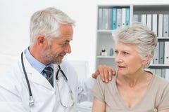 Patient supérieur féminin rendant visite à un docteur Photo stock