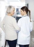 Patient supérieur handicapé se tenant avec le physiothérapeute At Rehab C Photo libre de droits