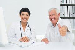 Patient supérieur heureux faisant des gestes des pouces avec le docteur Photos libres de droits