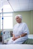 Patient supérieur inquiété s'asseyant sur le lit Photo libre de droits
