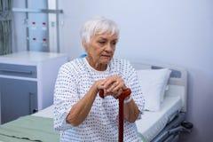 Patient supérieur inquiété s'asseyant sur le lit avec le bâton de marche Photographie stock