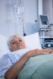 Patient supérieur inquiété se trouvant sur le lit Photographie stock libre de droits