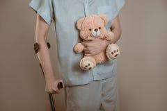 Patient sur des béquilles avec un jouet pour enfants Image stock
