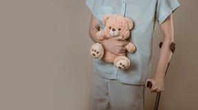Patient sur des béquilles avec un jouet pour enfants Photographie stock libre de droits