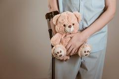 Patient sur des béquilles avec un jouet pour enfants Photos libres de droits
