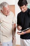 Patient sur les béquilles et le médecin Photographie stock