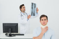 Patient in surgical collar while doctor examining spine xray behind Stock Photo