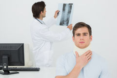 Patient in surgical collar while doctor examining spine xray behind Stock Image