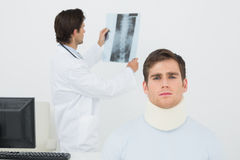 Patient in surgical collar with doctor examining spine xray behind Royalty Free Stock Photo