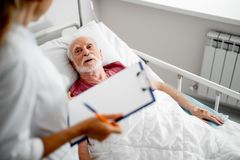 Patient talking with doctor while lying in bed royalty free stock photography