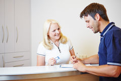 Patient talking with doctors assistant at reception Stock Image